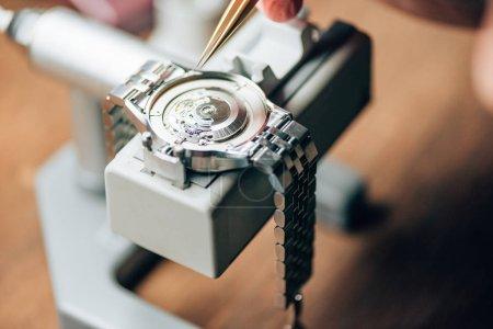 Photo pour Vue recadrée de l'horloger travaillant avec des brucelles et des montres-bracelets sur le porte-mouvement - image libre de droit