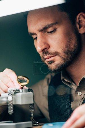 Photo pour Focus sélectif du bel horloger travaillant avec loupe et montre-bracelet sur le porte-mouvement - image libre de droit