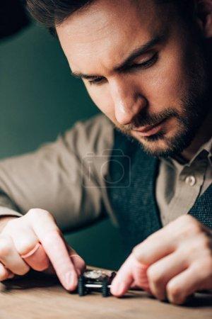 Photo pour Focus sélectif du beau horloger travaillant avec montre-bracelet sur le porte-mouvement sur la table - image libre de droit