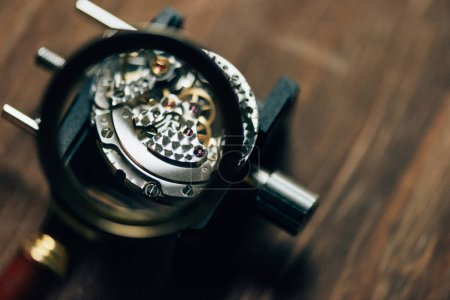 Photo for Selective focus of parts of mechanical wristwatch in magnifying glass on table - Royalty Free Image
