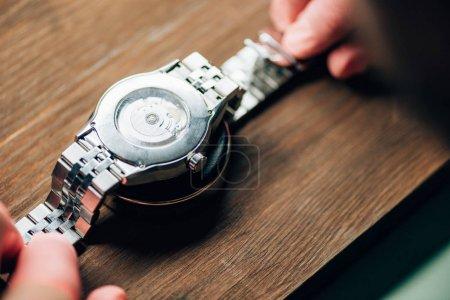 Photo pour Focalisation sélective de l'horloger tenant la montre-bracelet sur pied sur une table en bois - image libre de droit