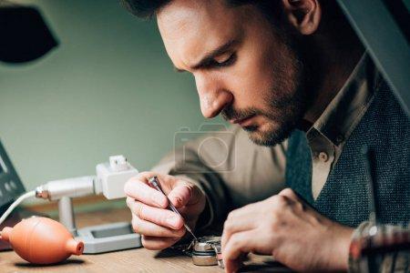 Photo pour Vue latérale de l'horloger travaillant avec tournevis et montre-bracelet par équipement sur la table - image libre de droit