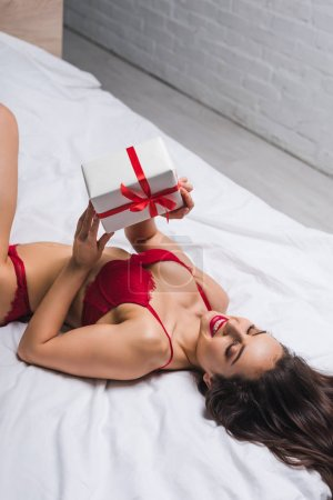 high angle view of sensual, happy girl in red lingerie lying in bed and holding white gift box