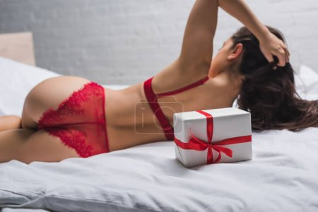 Photo for Back view of sexy girl in lingerie lying in bed near white gift box with red ribbon, panoramic shot - Royalty Free Image