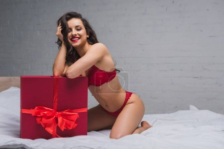 sexy in red lingerie smiling at camera while sitting in bed near large gift box