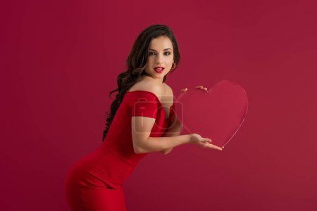 seductive, elegant girl holding paper heart and looking at camera isolated on red