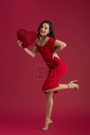 Photo for Smiling, elegant girl holding decorative heart while standing on one leg on red background - Royalty Free Image