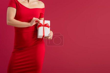 Photo pour Vue recadrée de sexy, élégante fille touchant ruban sur boîte cadeau tout en se tenant isolé sur rouge - image libre de droit