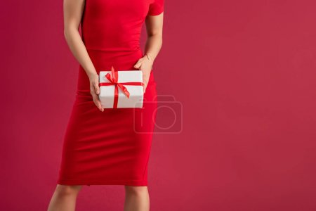 Photo for Cropped view of sexy, elegant girl holding gift box while standing isolated on red - Royalty Free Image