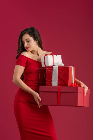 Photo for Sexy, smiling girl holding gift boxes while standing with closed eyes isolated on red - Royalty Free Image