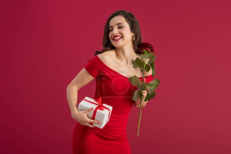Photo for Happy, elegant girl holding rose and gift box while smiling with closed eyes isolated on red - Royalty Free Image