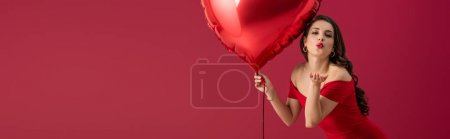Photo for Panoramic shot of seductive, elegant girl holding heart-shaped balloon and sending air kiss at camera isolated on red - Royalty Free Image