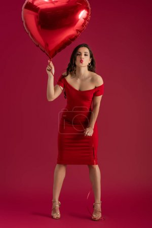 Photo for Sexy, elegant girl holding heart-shaped balloon and sending air kiss at camera on red background - Royalty Free Image