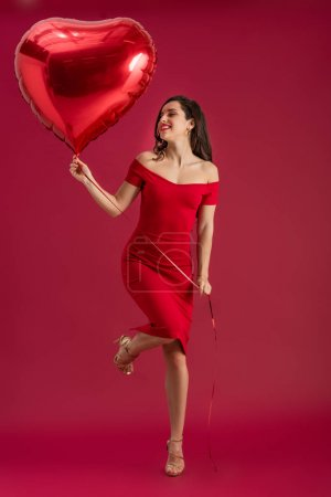 Photo for Happy, elegant girl holding heart-shaped balloon while standing on one leg on red background - Royalty Free Image