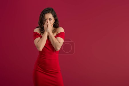 Photo for Upset, elegant girl covering face with hands while standing isolated on red - Royalty Free Image