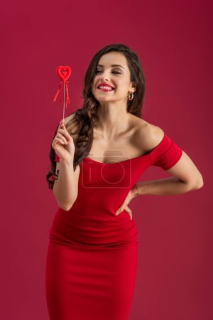 Photo for Cheerful, elegant girl smiling and looking away while holding toy heart on stick isolated on red - Royalty Free Image