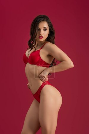 Photo for Seductive girl in lingerie looking away while touching panties isolated on red - Royalty Free Image