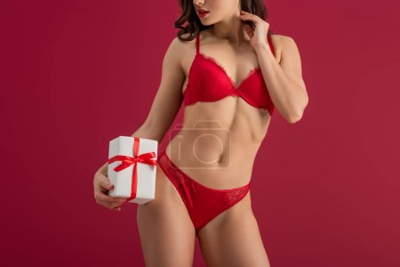 cropped view of sexy girl in lingerie holding white gift box isolated on red