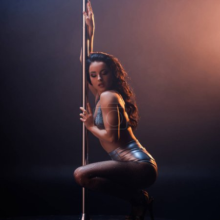 Photo for Attractive stripper in underwear sitting near pole on black and orange - Royalty Free Image