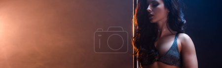 Photo for Panoramic shot of sexy woman in bra standing near pylon on blue and orange with smoke - Royalty Free Image