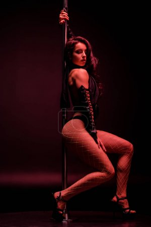 Photo for Seductive stripper dancing near pylon on black with red lighting - Royalty Free Image