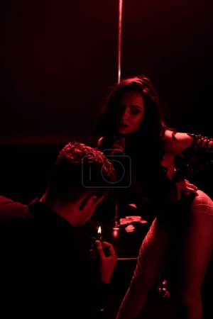 Photo for Man holding lighter while smoking near seductive stripper on black with red lighting - Royalty Free Image