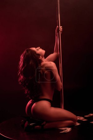 Photo for Young sexy woman with closed eyes dancing striptease on black with red lighting - Royalty Free Image