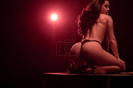 Photo for Seductive stripper in panties dancing striptease on black with red lighting - Royalty Free Image