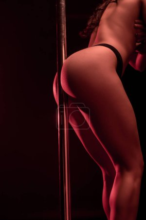 Photo for Cropped view of seductive stripper standing near pylon on black with red lighting - Royalty Free Image