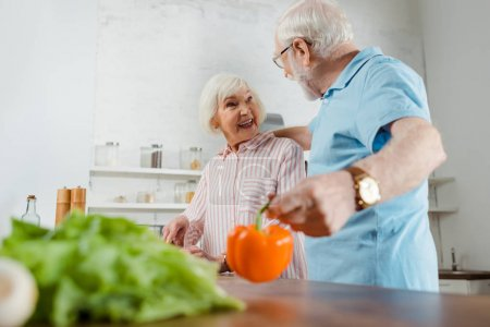 Photo for Selectie focus of senior man hugging smiling wife while holding bell pepper by kitchen table - Royalty Free Image