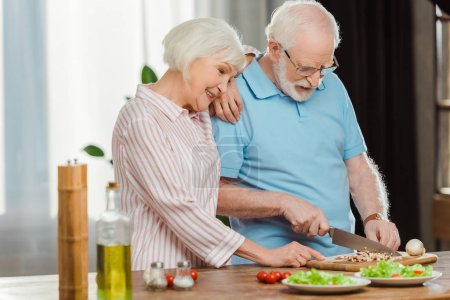 Photo for Smiling senior woman standing by husband cutting vegetables on kitchen table - Royalty Free Image