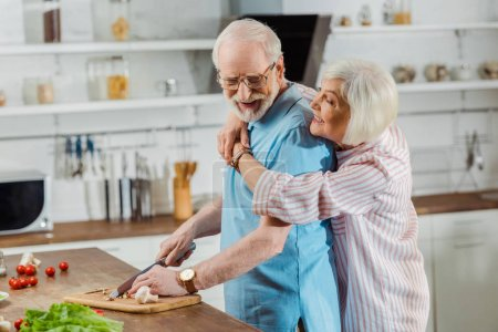 Photo for Side view of senior woman hugging husband during cooking on kitchen table - Royalty Free Image