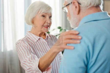 Photo for Selective focus of smiling senior woman embracing husband at home - Royalty Free Image