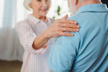 Enfoque selectivo de sonreír mujer mayor tocando marido a hombro en casa