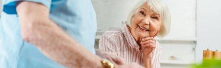 Photo pour Foyer sélectif de sourire femme âgée regardant mari à la maison, vue panoramique - image libre de droit