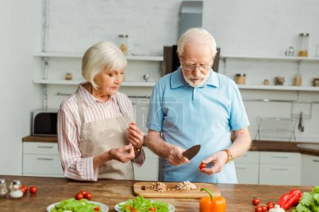 Senior couple cutting vegetables while cooking together in kitchen