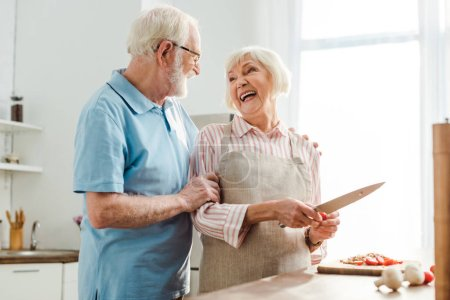 Photo for Senior man hugging smiling wife while cutting vegetables on kitchen table - Royalty Free Image