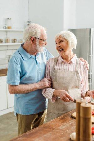 Photo pour Orientation sélective d'un homme âgé embrassant une femme souriante pendant la cuisson sur une table de cuisine - image libre de droit