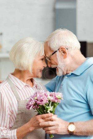 Photo pour Vue latérale d'un couple d'aînés tenant un bouquet et souriant les uns aux autres à la maison - image libre de droit