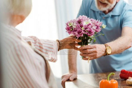 Photo for Cropped view of senior man giving bouquet to wife beside fresh vegetables on kitchen table - Royalty Free Image