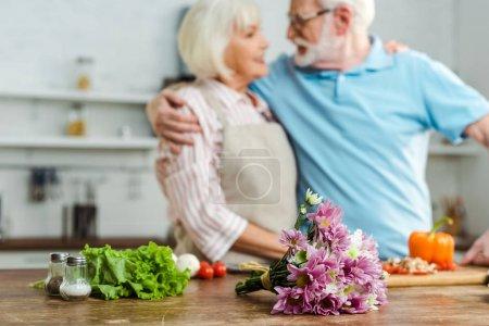 Photo pour Bouquet sélectif et légumes frais sur table et sourire couple de personnes âgées dans la cuisine - image libre de droit