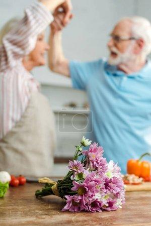 Photo pour Bouquet et légumes sur la table de la cuisine et danses de couple en arrière-plan - image libre de droit