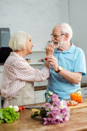 Photo pour Couple de personnes âgées s'alimentant mutuellement de tomates cerises au moyen de légumes et de bouquet sur une table de cuisine - image libre de droit