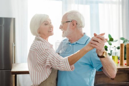 Photo for Side view of smiling senior couple looking at each other while dancing in kitchen - Royalty Free Image