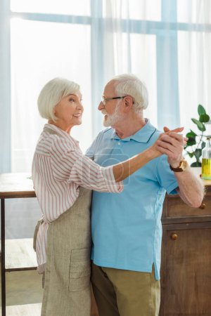 Photo pour Vue latérale d'un homme âgé dansant avec sa femme souriante sur un tablier dans la cuisine - image libre de droit