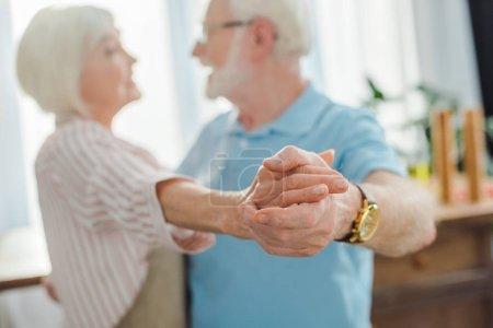 Photo pour Focus sélectif du couple d'aînés tenant la main pendant qu'ils dansent dans la cuisine - image libre de droit