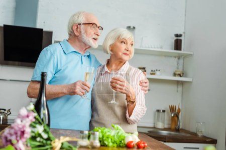 Photo for Selective focus of senior couple with glasses of champagne looking away beside bouquet and vegetables on kitchen table - Royalty Free Image