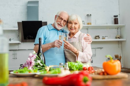 Photo for Selective focus of elderly couple smiling at camera while clinking with champagne by vegetables and bouquet on kitchen table - Royalty Free Image