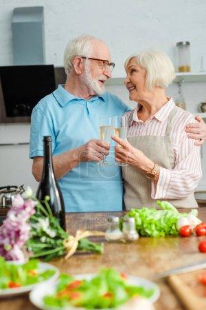 Photo pour Un couple d'aînés se sourit les uns aux autres tout en grillant du champagne au bouquet et des légumes sur une table de cuisine - image libre de droit