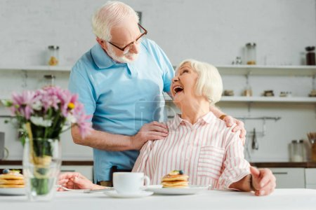 Photo for Selective focus of senior woman laughing while looking at husband by coffee and pancakes on table in kitchen - Royalty Free Image